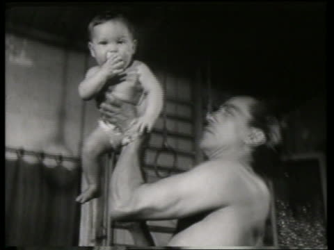 vídeos de stock, filmes e b-roll de black and white man holding standing baby in hand / no audio - fralda