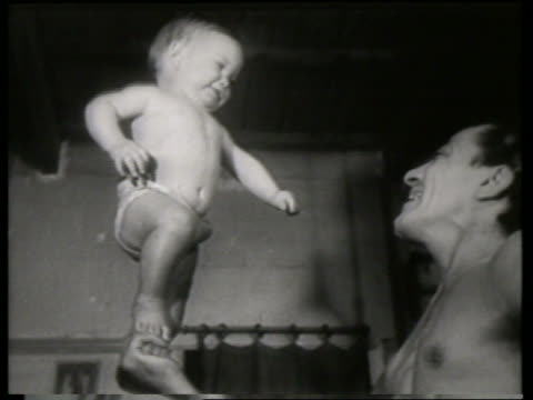 black and white man holding standing baby in hand / no audio - genderblend stock videos & royalty-free footage