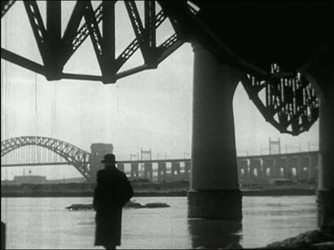 vídeos de stock, filmes e b-roll de 1937 black and white man in hat standing under triborough bridge and looking at hell gate bridge / new york city - hat