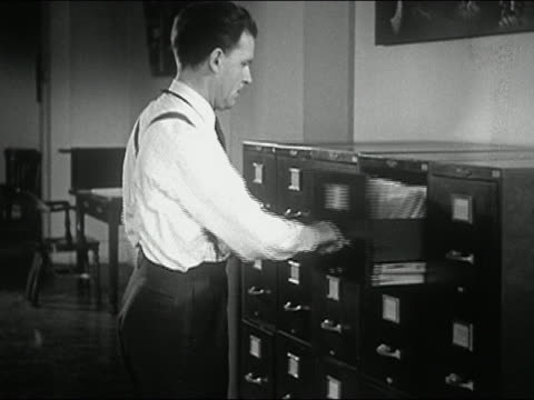 1944 black and white man looking through filing cabinet / removing folder / shutting drawer on finger - open drawer stock videos & royalty-free footage