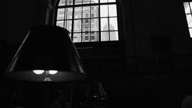 Black and white Manhattan with the view of the Empire State building through a window