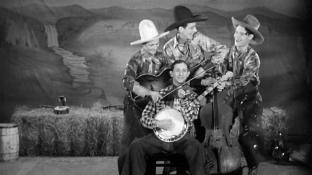 black and white medium shot 1930 four band members playing each other's instruments and singing - cowboy stock videos & royalty-free footage