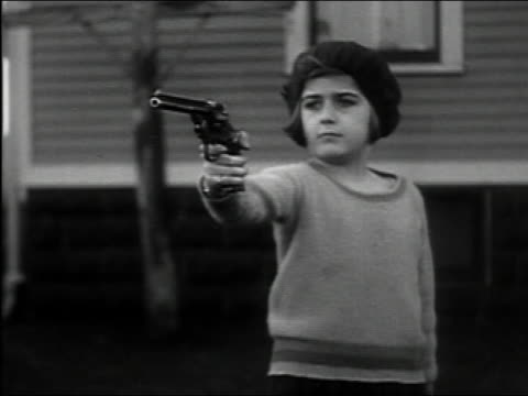black and white medium shot 5-year-old girl aims and fires pistol - arma da fuoco video stock e b–roll