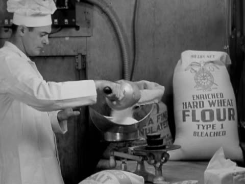 1942 black and white medium shot baker pouring flour from scoop and measuring it on scale / camp lee virginia - sack stock videos & royalty-free footage