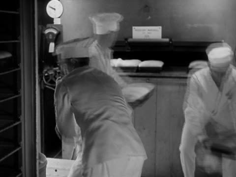 1942 black and white medium shot bakers removing baked bread and putting unbaked dough into oven / camp lee virginia - oven mitt stock videos and b-roll footage