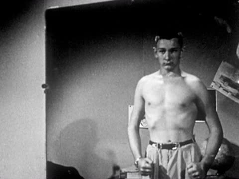 stockvideo's en b-roll-footage met 1953 black and white medium shot bare-chested teenage boy flexing muscles and looking at himself in mirror / audio - tienerjongens