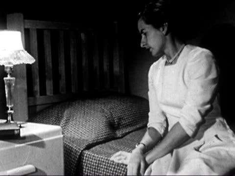1953 black and white medium shot depressed teenage girl sitting on bed with head in hands / lying down on bed / audio - sulking stock videos & royalty-free footage