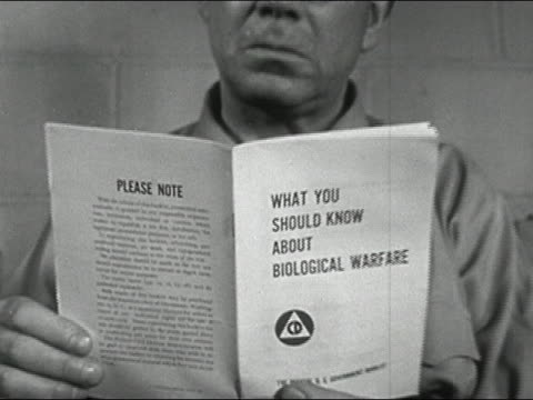 1952 black and white medium shot dolly shot close up man reading pamphlet titled 'What You Should Know About Biological Warfare'