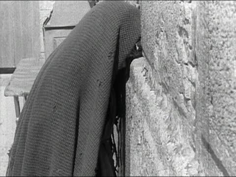 1936 black and white medium shot elderly jewish woman praying at wailing (western) wall, jerusalem, israel / audio - jerusalem old city stock videos and b-roll footage