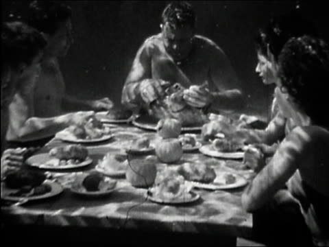 1946 black and white medium shot family eating thanksgiving dinner underwater / father tearing off turkey leg - thanksgiving plate stock videos & royalty-free footage
