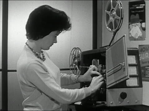 1963 black and white medium shot female teacher setting up projector to show filmstrip / audio - projection equipment stock videos & royalty-free footage
