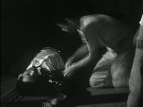 1955 black and white medium shot five young men beating older man in suit and stealing his wallet