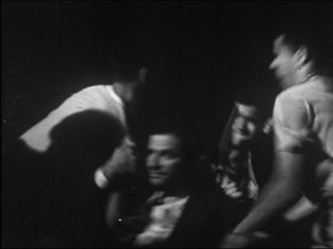 1955 black and white medium shot five young men running into view, beating man in suit and dragging him off - gang stock videos and b-roll footage