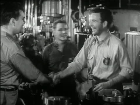 1945 black and white medium shot four men gathering around and congratulating another man in machine shop - nedtoning bildbanksvideor och videomaterial från bakom kulisserna