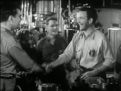 vídeos y material grabado en eventos de stock de 1945 black and white medium shot four men gathering around and congratulating another man in machine shop - fundido en negro