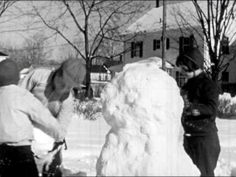 1945 black and white medium shot girl packing snow on body of snow man / younger boy hands older boy snowball for the head / audio - mitten stock videos and b-roll footage