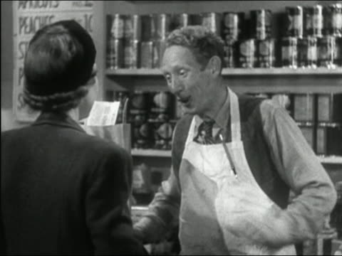 stockvideo's en b-roll-footage met 1941 black and white medium shot grocer chatting to woman and passing grocery bag to her / woman leaving - kruidenier