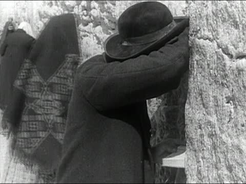 1936 black and white medium shot jewish man and woman praying at the wailing (western) wall, jerusalem, israel / audio - jerusalem old city stock videos and b-roll footage