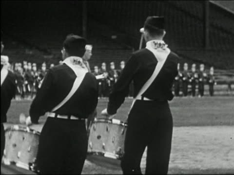 1955 black and white medium shot line of buglers and drummers rotating / pan marching feet with white spats - marching band stock videos and b-roll footage