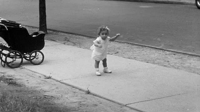 1934 black and white medium shot little girl toddling on sidewalk and smiling at CAM / Huntington, Long Island, NY