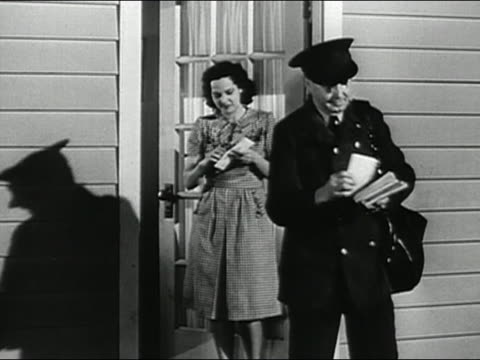vidéos et rushes de 1947 black and white medium shot mailman delivering letter to woman / son and daughter gathering around to read it / audio - poste