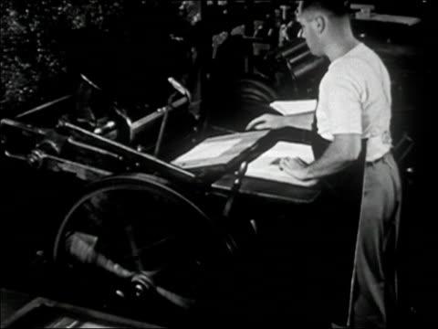 stockvideo's en b-roll-footage met 1947 black and white medium shot man copies on printing press - drukker