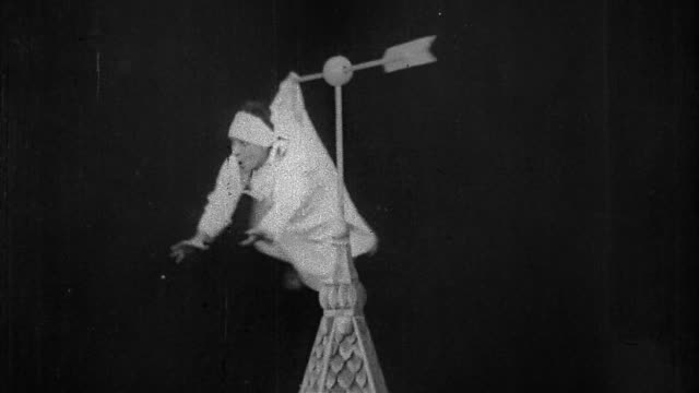 "1906 black and white medium shot man hanging from spinning weather vane by pajamas and falling / ""dream of a rarebit fiend"" - anno 1906 video stock e b–roll"