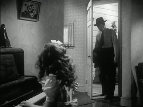1945 black and white medium shot man in shirt and tie entering front door of house with girl at piano in foreground