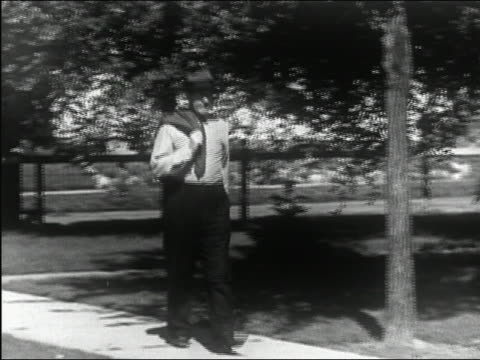 1945 black and white medium shot man in shirt and tie with jacket slung over shoulder walking through sunny suburb - shirt and tie stock videos & royalty-free footage