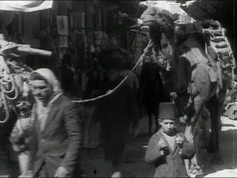 stockvideo's en b-roll-footage met 1936 black and white medium shot man leading group of camels through crowded street / damascus, syria / audio - 1936