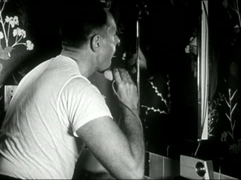 1958 black and white medium shot man shaving with electric razor in bathroom mirror/ audio - electric razor stock videos and b-roll footage