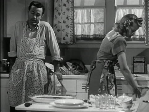 1945 black and white medium shot man talking at sink / woman giving man dish to re-dry / couple laughing - abwaschen stock-videos und b-roll-filmmaterial