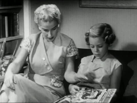 1956 black and white medium shot mother and daughter sitting on sofa / mother reading girl's magazines / audio - magazine stock videos & royalty-free footage