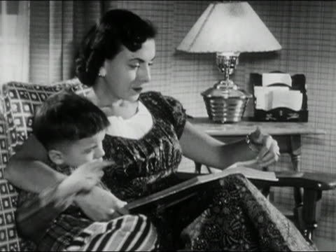 vídeos de stock e filmes b-roll de 1956 black and white medium shot mother sitting in chair with arm around young son  / reading book to boy / audio - família com um filho