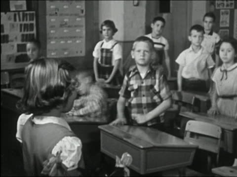 stockvideo's en b-roll-footage met 1955 black and white medium shot pan girl getting up from seat to lead class in pledge of allegiance / pan class reciting - 1955
