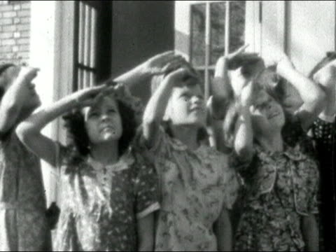 1935 black and white medium shot pan primary school children saluting flag with arms in air/ audio - saluting stock videos & royalty-free footage