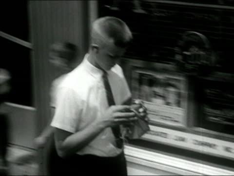 1958 black and white medium shot pan teenager walking down street listening to transistor radio with earphone/ audio - radio stock videos and b-roll footage