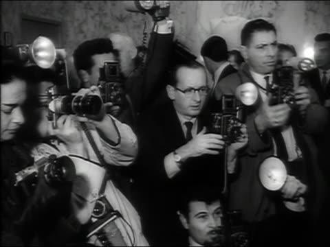 1963 black and white medium shot paparazzi taking photos at the premiere of The Ugly American / Bangkok