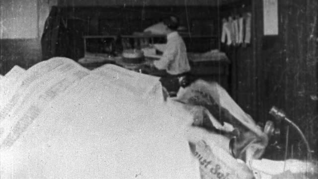 "1921 black and white medium shot stressed-out man (eddie lyons) emerging from pile of papers on desk / ""peace and quiet"" - dokument stock-videos und b-roll-filmmaterial"
