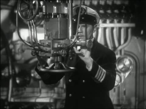 1941 black and white medium shot submarine captain looking through periscope - inside of stock videos and b-roll footage