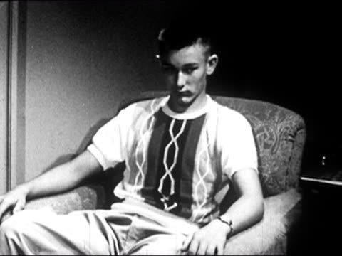 1953 Black and white medium shot sullen teenage boy sitting in armchair / talking and gesturing animatedly / zoom out arguing with parents / AUDIO