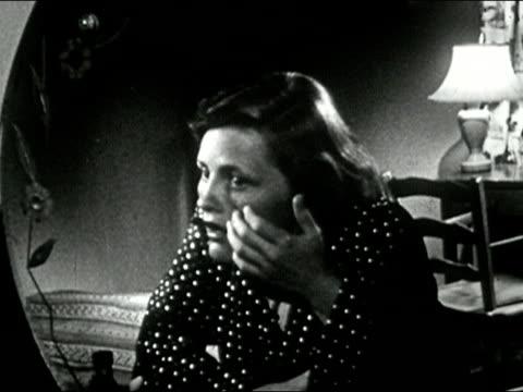 1953 black and white medium shot teenage girl examining her face in mirror / audio - 産みの苦しみ点の映像素材/bロール