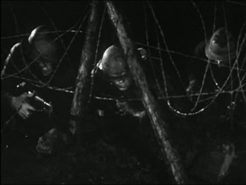 1955 black and white medium shot three wwii soldiers crawling under barbed wire at night with flash going off and dirt flying - arma da fuoco video stock e b–roll