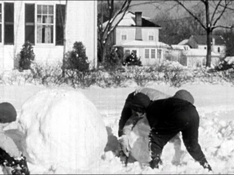 1945 black and white medium shot two boy and girl lifting large snowball / making snowman / audio - mitten stock videos and b-roll footage