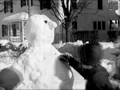 1945 black and white medium shot two boys and girls adding nose and eyes to snowman / decorating snowman with buttons and tin can hat / audio - mitten stock videos and b-roll footage