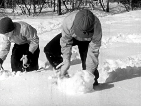 1945 black and white medium shot two boys playing in the snow / rolling snowballs / audio - mitten stock videos and b-roll footage