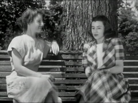 1950 black and white medium shot two girls sitting down on bench and chatting / columbia, missouri - flüstern stock-videos und b-roll-filmmaterial