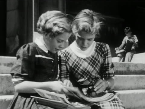 vídeos de stock e filmes b-roll de 1956 black and white medium shot two young girls sitting on steps reading comic books / audio - 1956