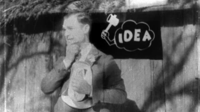 "vídeos de stock e filmes b-roll de 1928 black and white medium shot walter lantz thinking / being hit on head by animated ""idea"" hammer / ""barnyard rivals"" - ideas"