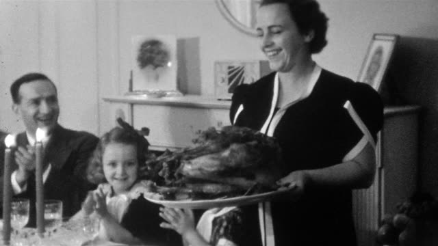stockvideo's en b-roll-footage met 1937 black and white medium shot woman (mrs. saracen) carrying turkey into dining room on thanksgiving /family applauding - 1930